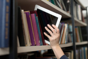 tablet picked with hand from book shelf in the library